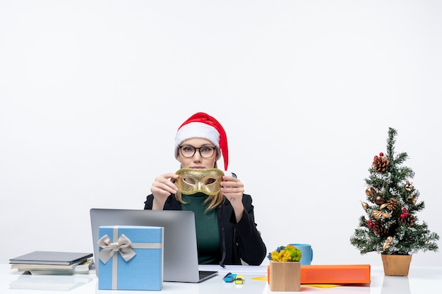 Jeune femme avec des lunettes de chapeau de père noël et un masque assis à une table avec un arbre de noël et un cadeau