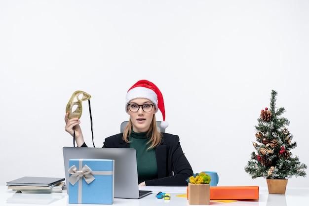 Jeune femme avec des lunettes de chapeau de père noël et tenant un masque assis à une table avec un arbre de noël et un cadeau
