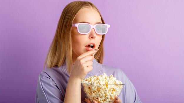 Jeune femme à lunettes de cinéma regardant un film en 3d au cinéma. visionneuse de film adolescente souriante dans des verres mangeant du pop-corn isolé sur fond de couleur violet avec espace de copie. bannière web longue.