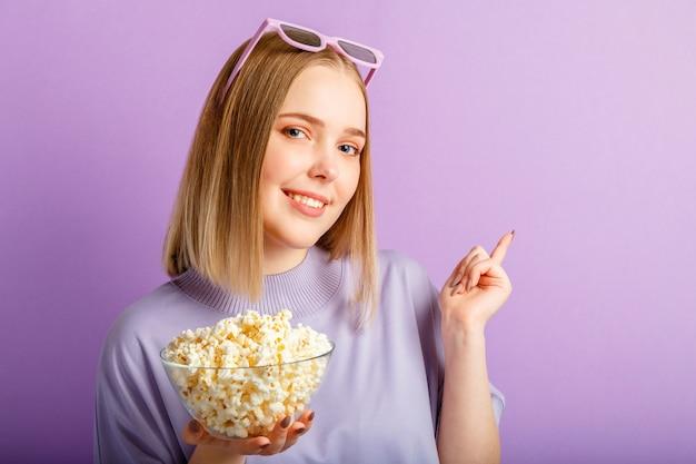 Jeune femme à lunettes de cinéma regardant un film en 3d. visionneuse de film adolescente souriante dans des verres avec spectacle de pop-corn avec votre main sur l'espace de copie isolé sur fond de couleur violet.