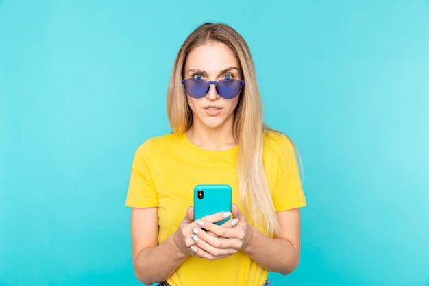 Jeune femme à lunettes debout sur bleu isolé en regardant la caméra. jeunesse et technologie.