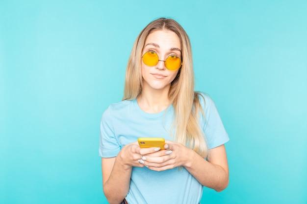 Jeune femme à lunettes debout sur bleu isolé en regardant la caméra.