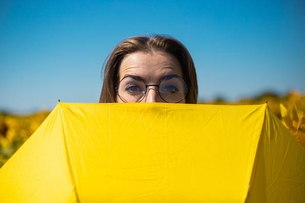 Jeune femme avec des lunettes furtivement derrière un parapluie jaune sur un champ de tournesol.
