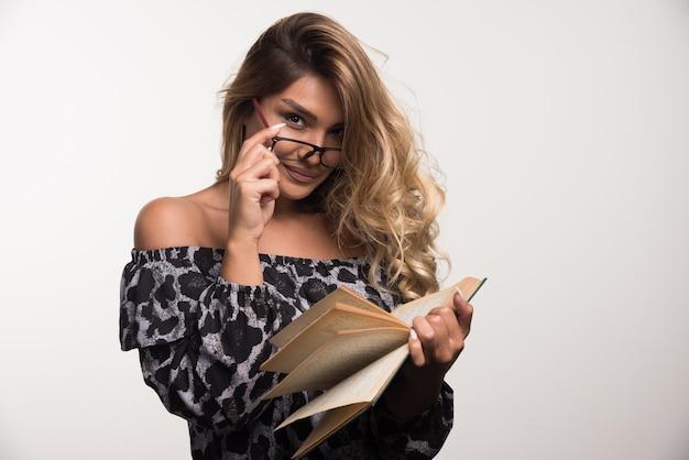 Jeune femme à lunettes en lisant un livre sur un mur blanc.