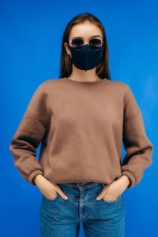 Jeune femme à lunettes, masque médical et sweat à capuche qui pose en studio sur fond bleu