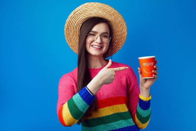 Jeune femme avec des lunettes pointe au café à emporter a une expression joyeuse