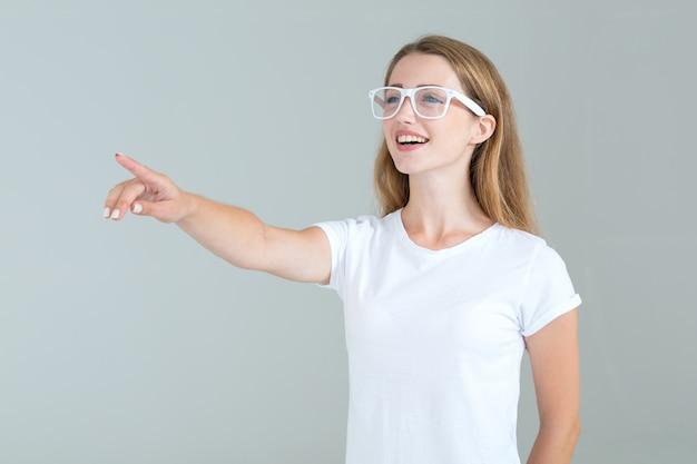 Jeune femme à lunettes pointe un doigt sur le côté, isolé sur fond gris