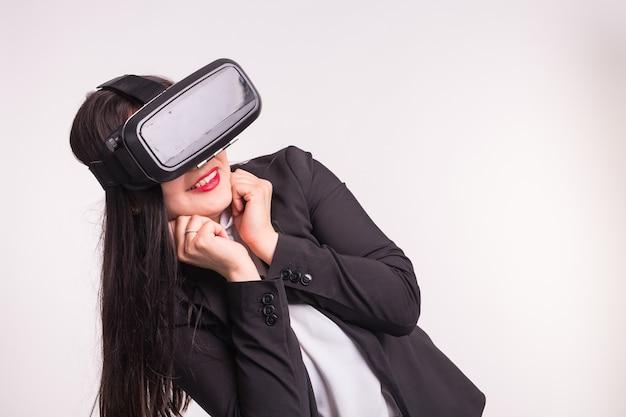 Jeune femme avec des lunettes de réalité virtuelle sur un mur blanc.