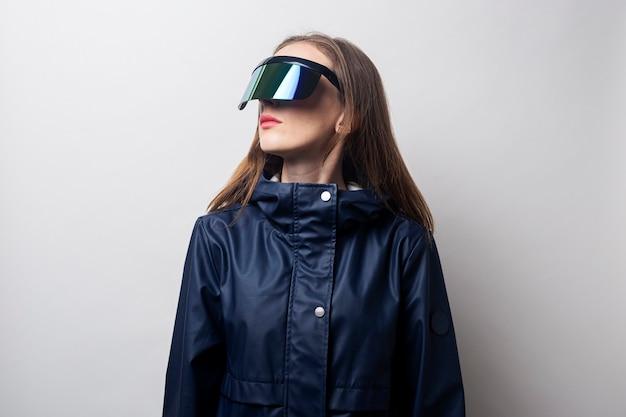 Jeune femme à lunettes de réalité virtuelle regarde sur le côté sur un fond clair.