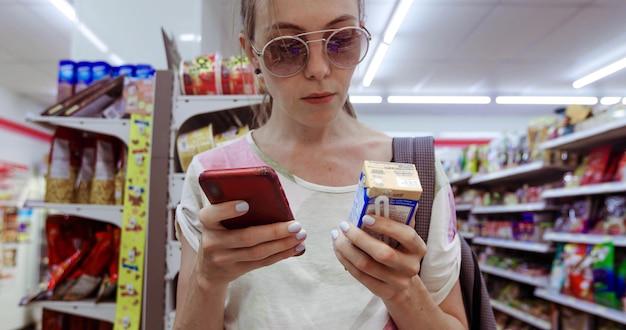 Jeune femme à lunettes de soleil debout dans l'épicerie et à l'aide de téléphone en vérifiant la case de boisson fraîche