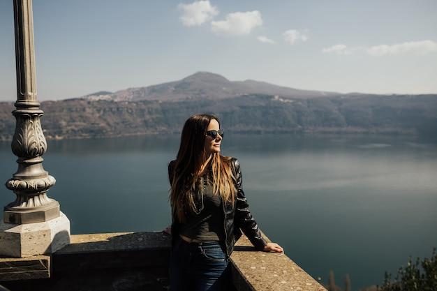 Jeune femme avec des lunettes de soleil avec lac et montagnes derrière