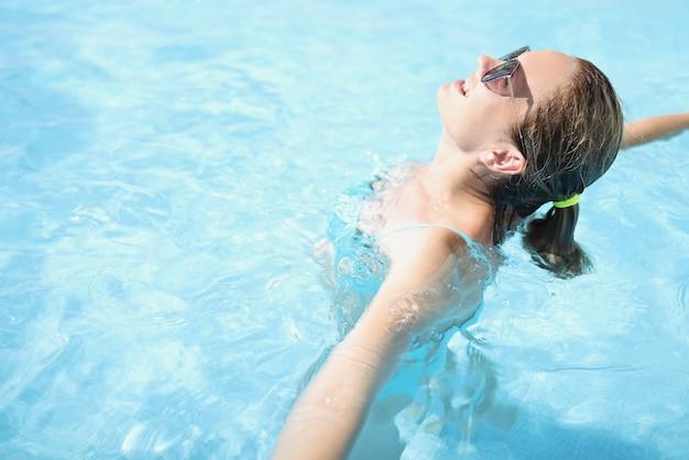 Jeune femme à lunettes de soleil profite de vacances dans la piscine en gros plan