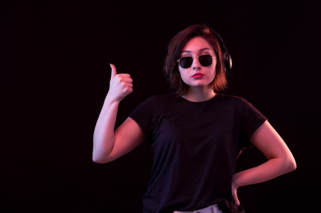 Jeune femme, à, lunettes soleil, et, t-shirt noir, utilisation, écouteurs