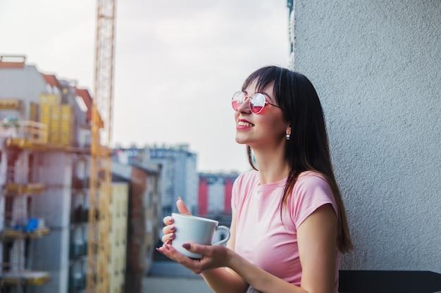Jeune femme à lunettes de soleil avec une tasse de café rester sur le balcon