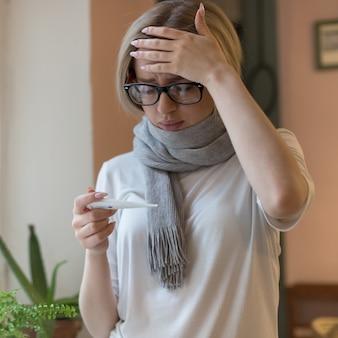Jeune femme à lunettes et t-shirt, enveloppé dans un foulard ayant des symptômes du rhume, regardant un thermomètre, touchant son front. virus, saison grippale