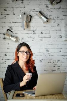 Jeune femme avec des lunettes tient une tasse de café