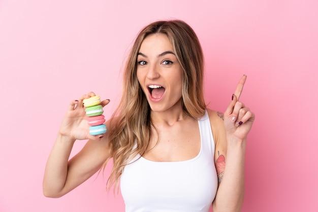 Jeune femme avec des macarons pointant vers le haut une excellente idée