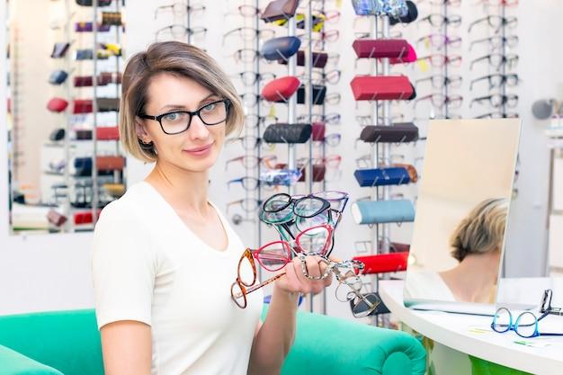 Jeune femme en magasin d'optique choisissant de nouvelles lunettes avec un opticien. lunettes dans le magasin d'optique. une femme choisit des lunettes. beaucoup de verres à la main. ophtalmologie.