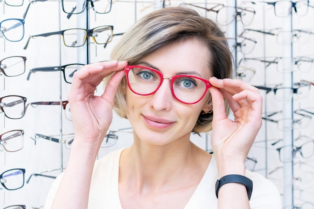 Jeune femme en magasin d'optique choisissant de nouvelles lunettes avec un opticien. lunettes dans le magasin d'optique. une femme choisit des lunettes. émotions. ophtalmologie.