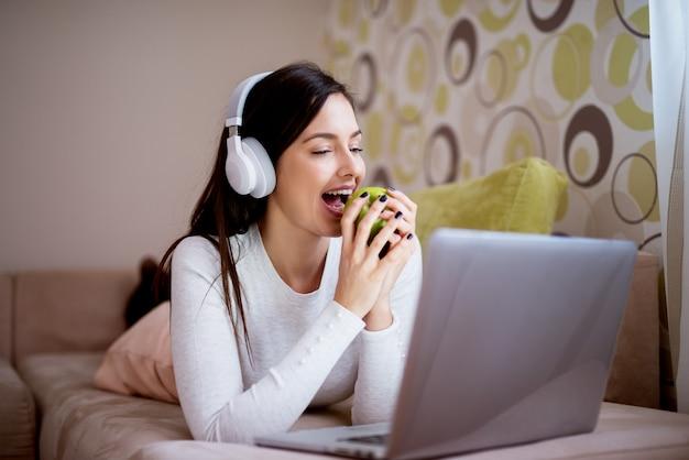 Jeune femme magnifique, allongée sur son canapé, mange une pomme appuyée sur les coudes, sourit pendant qu'elle apprécie la musique d'un ordinateur portable avec des écouteurs.