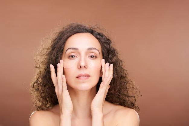 Jeune femme magnifique aux cheveux ondulés foncés mettant des taches sous les yeux sur son visage après avoir purifié la peau avec du toner