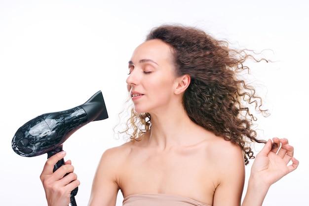 Jeune femme magnifique aux yeux fermés séchant ses beaux longs cheveux bruns ondulés avec un appareil électrique après les avoir lavés le matin