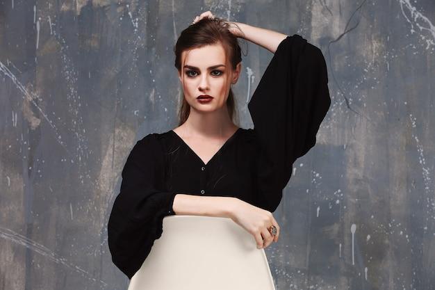 Jeune femme magnifique en chemise noire avec beau maquillage posant sur fond gris
