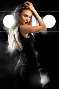 Jeune femme magnifique avec des lèvres rouges en costume noir avec des fesses rondes sexy en regardant la caméra en studio sur un mur sombre avec de la fumée