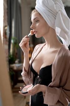Jeune femme magnifique en lingerie noire et pyjama beige debout devant le miroir dans la chambre et appliquant de la poudre sur le visage après le bain