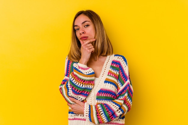 Jeune femme maigre caucasienne isolée sur fond jaune suspect, incertain, vous examine.