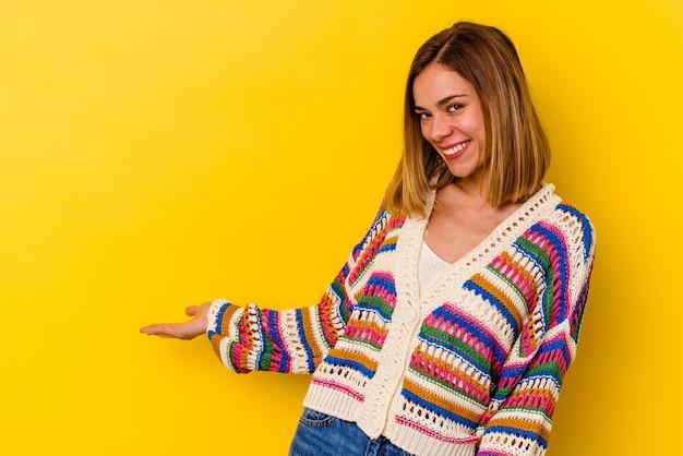 Jeune femme maigre caucasienne isolée sur jaune montrant une expression de bienvenue.