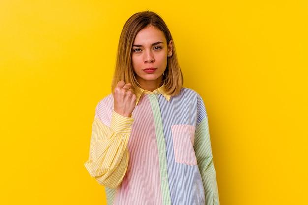 Jeune femme maigre caucasienne isolée sur jaune montrant le poing, expression faciale agressive.