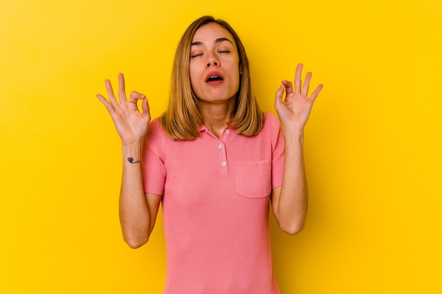 Jeune femme maigre caucasienne isolée sur un mur jaune se détend après une dure journée de travail, elle effectue du yoga.