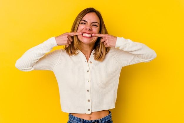 Jeune femme maigre caucasienne isolée sur le mur jaune sourit, pointant du doigt la bouche.