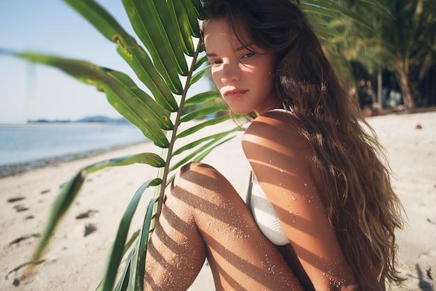 Jeune femme maigre en maillot de bain bikini blanc tenant une feuille de palmier en train de bronzer sur la plage tropicale.