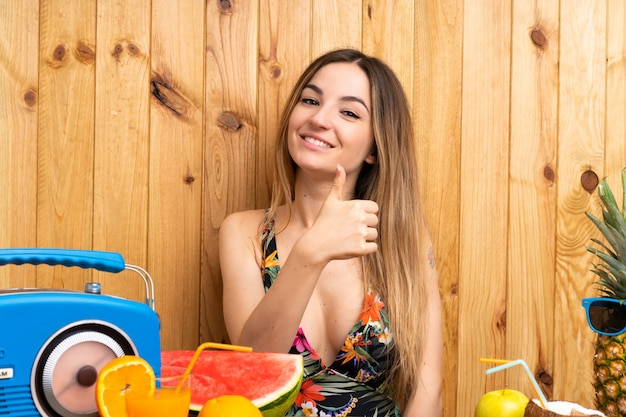 Jeune femme en maillot de bain avec beaucoup de fruits donnant un geste du pouce levé