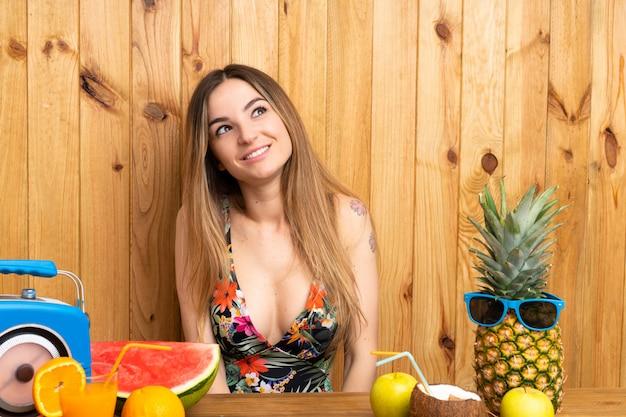 Jeune femme en maillot de bain avec beaucoup de fruits en riant et levant