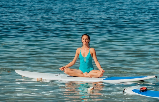 Jeune femme en maillot de bain bleu faisant du yoga à bord