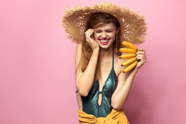 Jeune femme en maillot de bain et un chapeau avec ananas à la main, fête amusante, plage à la maison
