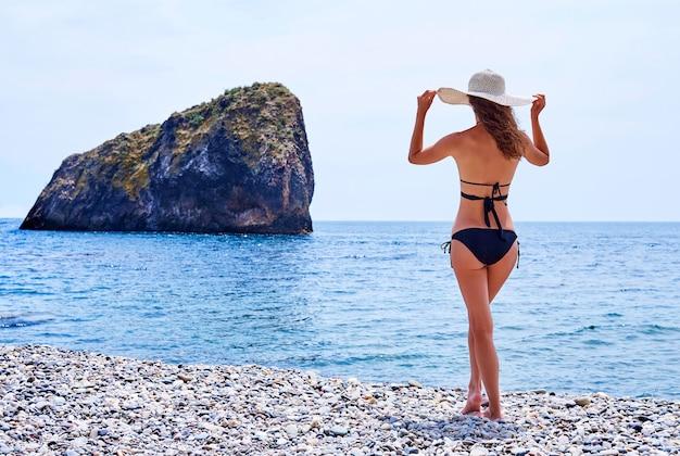 Jeune femme en maillot de bain avec un chapeau sur la plage.