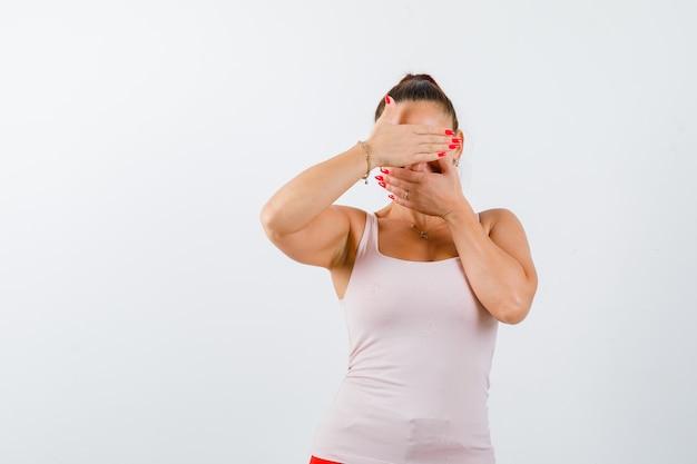 Jeune femme en maillot de bain fermant le visage avec les mains et à la jolie vue de face.