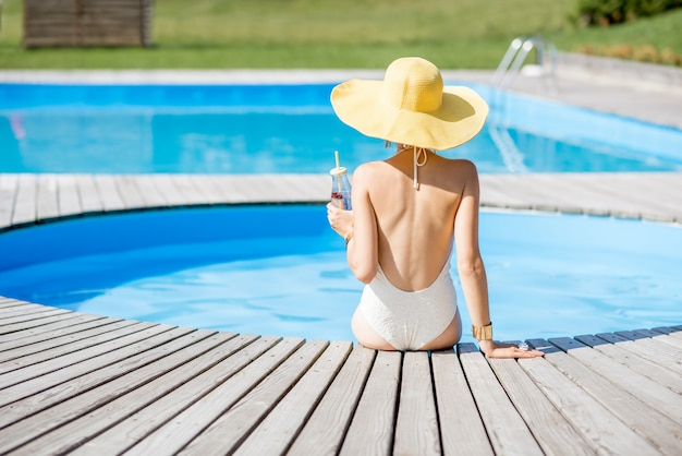 Jeune femme en maillot de bain avec un grand chapeau jaune se détendre avec une bouteille de boisson fraîche assise au bord de la piscine à l'extérieur