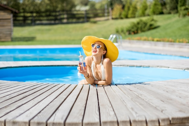 Jeune femme en maillot de bain avec grand chapeau jaune se détendre avec une bouteille de boisson fraîche assise au bord de la piscine à l'extérieur