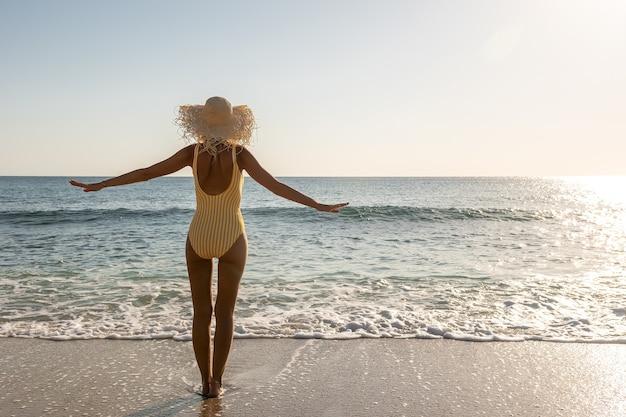 Jeune femme en maillot de bain avec les mains écartées sur une plage de sable.