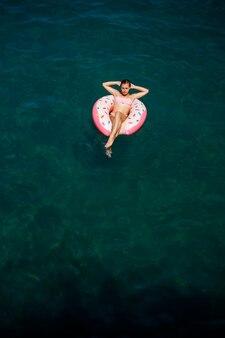Jeune femme en maillot de bain nage sur un anneau gonflable dans la mer. concept de vacances d'été.