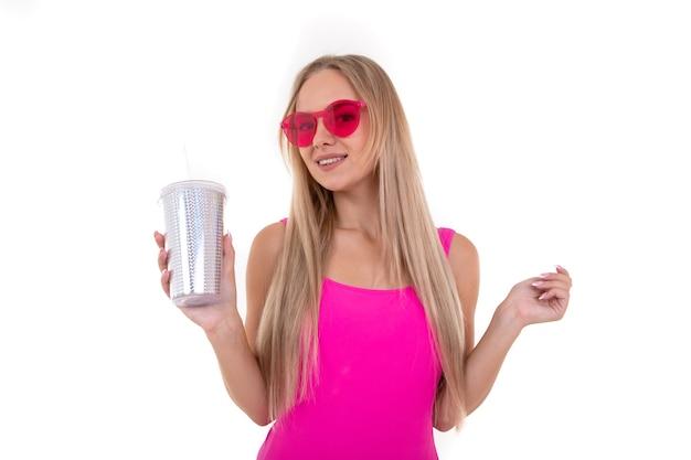 Une jeune femme en maillot de bain rose boit de la limonade sur fond blanc