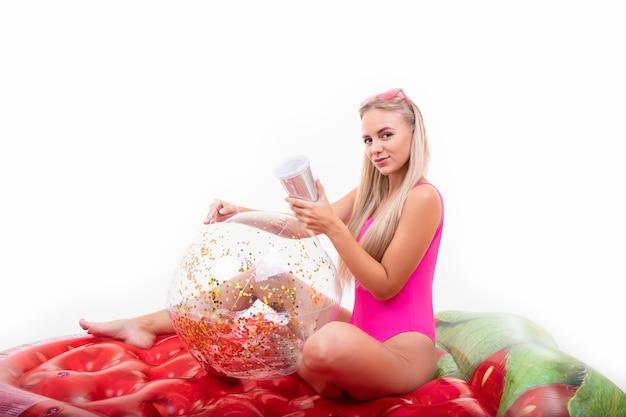 Une jeune femme en maillot de bain rose et lunettes est assise sur un matelas pneumatique