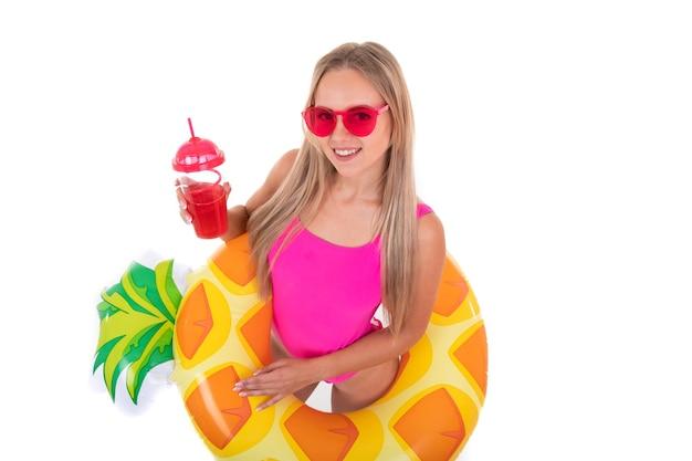 Une jeune femme en maillot de bain rose et lunettes tient un cercle de natation gonflable et boit de la limonade