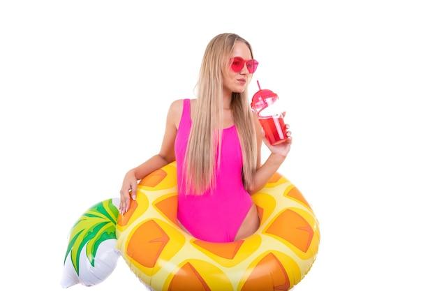 Une jeune femme en maillot de bain rose et lunettes tient un cercle de natation gonflable
