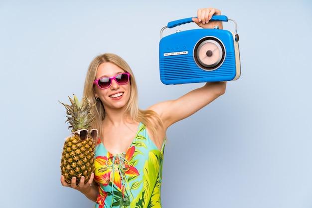 Jeune femme en maillot de bain tenant un ananas avec des lunettes de soleil et une radio